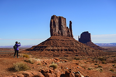 Woman photographing butte in Monument Valley, Arizona, USA