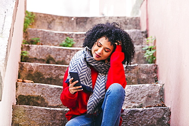 Young woman with smart phone sitting on steps