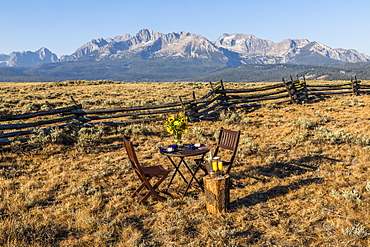 Dining table and chairs in field by mountain in Stanley, Idaho
