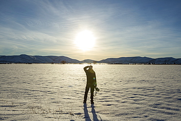 Senior man with camera in snow field in Picabo, Idaho