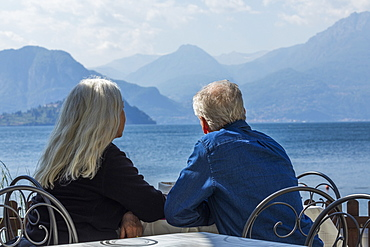 Gray haired couple sitting by Lake Como in Lombardy, Italy