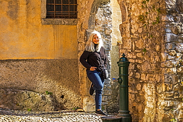 Mature woman leaning on stone arch in Lake Como, Italy