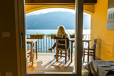 Mature woman sitting on balcony by Lake Como in Lombardy, Italy