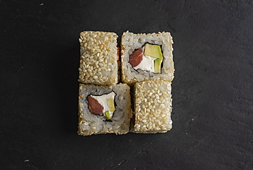 Sushi with sesame seeds on black surface