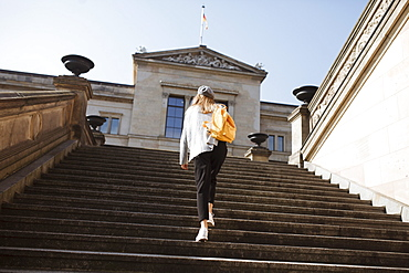 Young woman walking on steps in Berlin, Germany