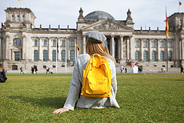 Young woman sitting in park by Reichstag in Berlin, Germany