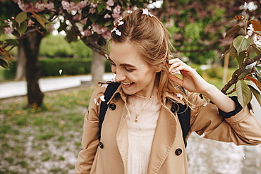 Smiling woman among falling petals from tree in bloom