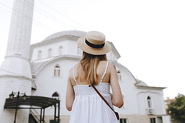 Young woman in straw hat by building in Marmaris, Turkey