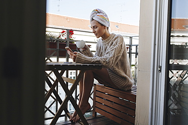 Young woman drinking coffee on apartment balcony