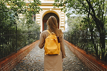 Young woman with yellow backpack walking in park
