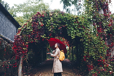Woman holding umbrella by vine covered arch