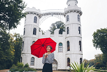 Woman holding red umbrella by Schloss Pfaueninsel in Potsdam, Germany