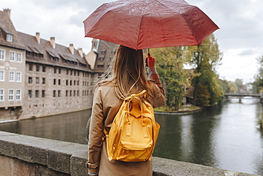 Woman wearing backpack holding umbrella by river in Nuremberg, Germany