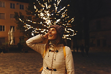 Smiling woman wearing coat by fairy lights in tree at night