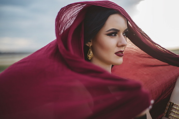 Windswept woman wearing red headscarf and lipstick