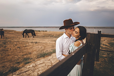 Young couple embracing in field by horses