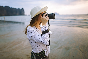 Young woman photographing on beach in Krabi, Thailand