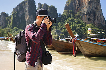 Young man photographing on beach in Krabi, Thailand