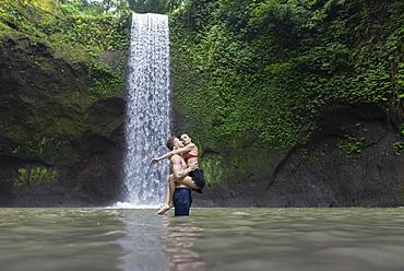 Young man carrying young woman in river by Tibumana Waterfall in Bali, Indonesia