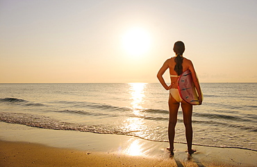 Woman holding surfboard on beach at sunset