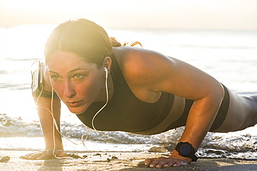 Woman wearing headphones doing push-up on beach