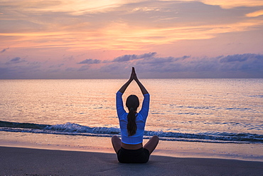 Woman practicing yoga on beach at sunset