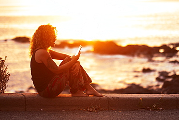 Woman using smart phone by beach at sunset
