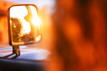 Reflection in wing mirror of smiling woman wearing sunglasses