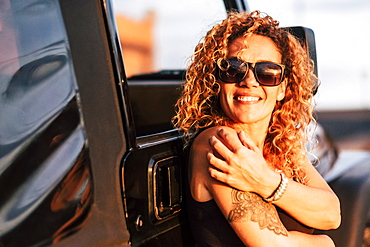 Smiling woman wearing sunglasses with arm tattoo