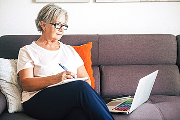 Senior woman holding pen using laptop on sofa