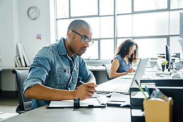 Man holding pen using laptop in office