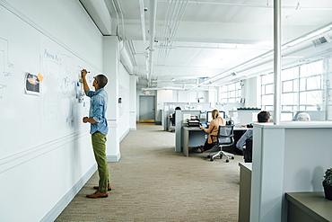 Man writing on whiteboard in office