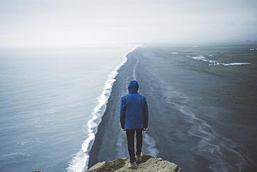 Man wearing blue coat above beach in Vik, Iceland