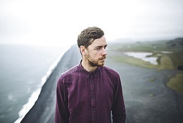 Bearded man above beach in Vik, Iceland