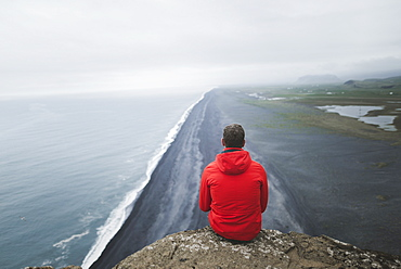 Man wearing red coat sitting above beach in Vik, Iceland
