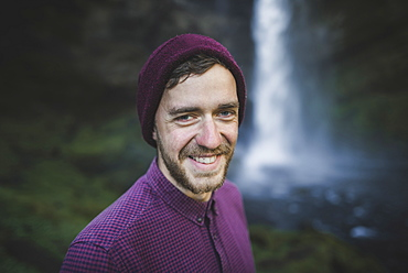 Portrait of smiling young man by Kvernufoss waterfall in Iceland