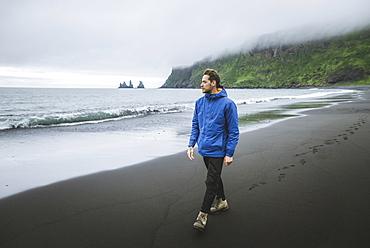 Man walking on beach in Vik, Iceland