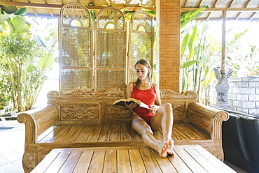 Woman wearing swimsuit reading book on wooden sofa