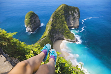 Legs of woman sitting above Kelingking Beach in Nusa Penida, Indonesia