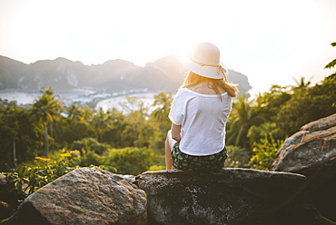 Woman wearing straw hat sitting on rock at sunset on Phi Phi Islands, Thailand