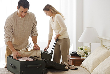 Couple unpacking in hotel room