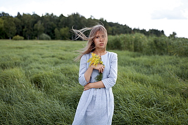 Windswept woman holding yellow flowers in field