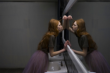 Young woman leaning on bathroom mirror