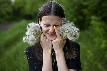 Teenage girl with her eyes closed holding dandelions