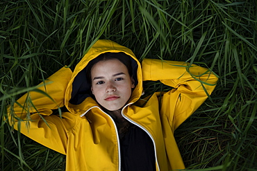 Teenage girl wearing yellow raincoat lying on grass