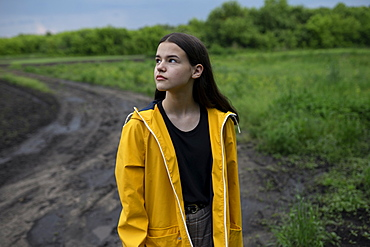 Teenage girl wearing yellow raincoat on country road