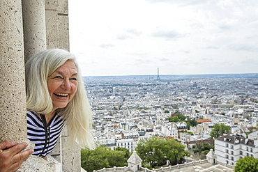 Smiling woman by cityscape from Sacre Coeur in Paris, France