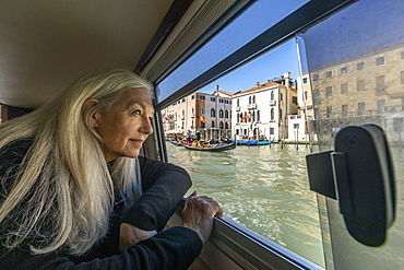 Woman looking out of boat window on Grand Canal, Venice, Italy