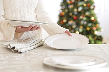 Woman setting table at Christmas