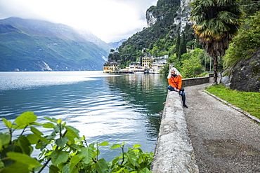 Woman on waterfront in Riva Del Garda, Lombardy, Italy